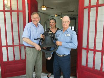 Jon Moore and Linda Garcia accepting an antique steeple bell from Jack Helm of Helm Vault